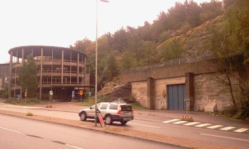 Fult parkeringshus och ingång till skyddsrum mellan Kvarnholmsvägen och Henriksdalsberget