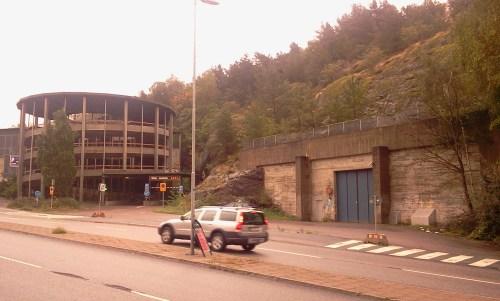 Fult parkeringshus och ingång till reningsverket m mellan Kvarnholmsvägen och Henriksdalsberget
