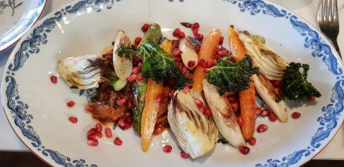 Svarta belugalinser serveras med bakad fänkål, vårprimörer rökt Vegme samt sallad på grönkål, spenat och granatäpple