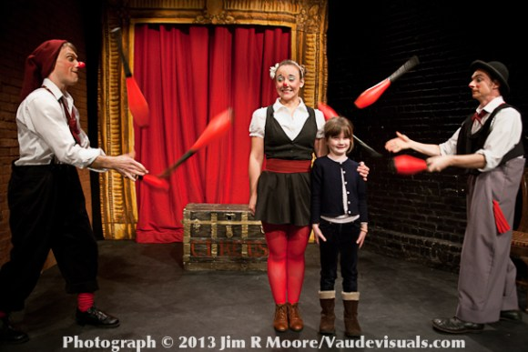 A young audience member volunteers to stand in the middle of 2 juggling clowns.