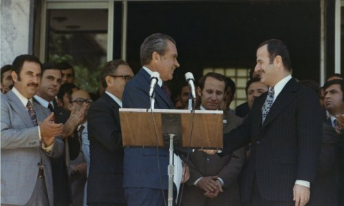 Richard Nixon and Syrian President Hafez al-Assad shake hands as other officials, including Henry Kissinger, watch.