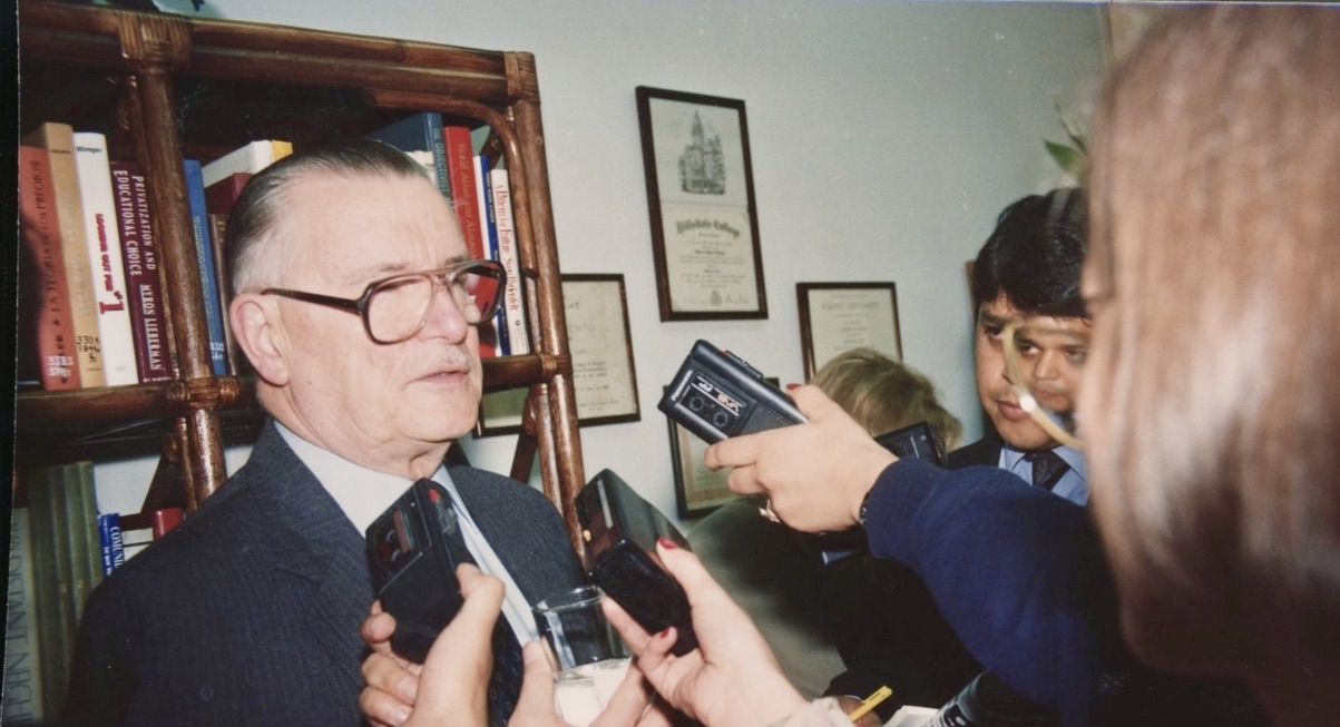 James M. Buchanan surrounded by members of the media.