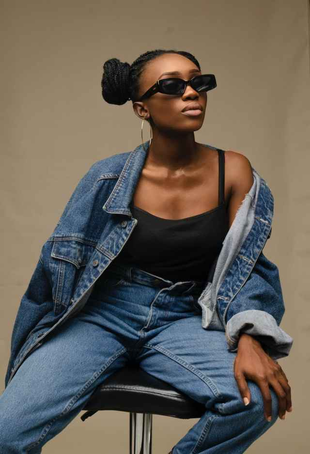 stylish black woman in trendy outfit and sunglasses