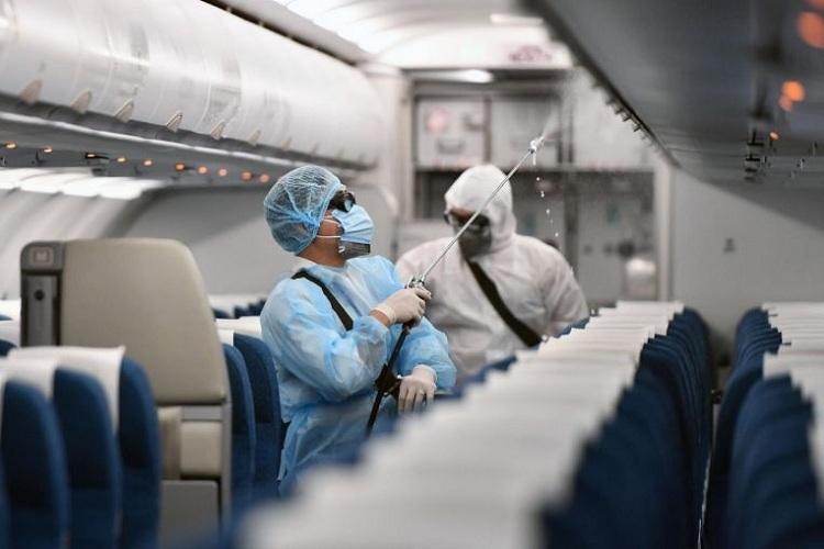 Nhân viênmặc đồ bảo hộ khử trùng máy bay của Vietnam Airlinestại sân bay quốc tế Nội Bài, Hà Nội. Ảnh: AFP.