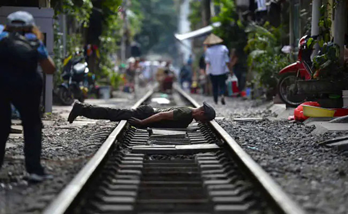 A tourist poses for a photo on a railway track. Photo by AFP/Nhac Nguyen.