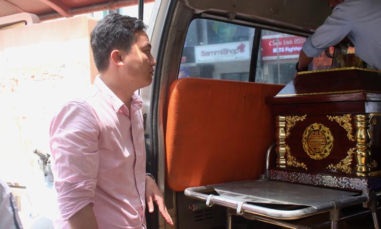 Nghị (áo hồng)nán lại vớigia đình, chờ đến lúc đưa quan tài bé lên xe. Ảnh: Diệp Phan
