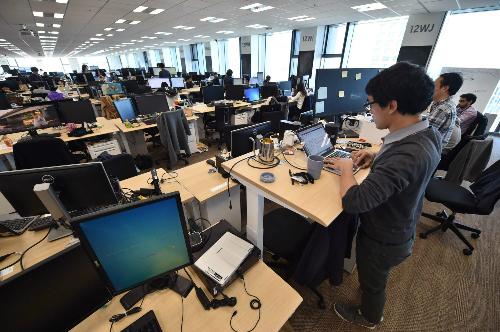 Nhân viên sử dụng bàn làm việc di động để có thể đứng, ngồi tùy ý tại Rakuten. Ảnh: AFP.