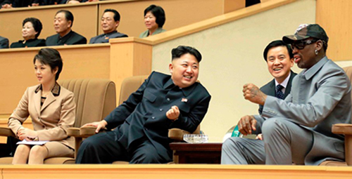 [Caption]A picture made available by North Korea shows supreme leader Kim Jong Un, center, with his wife, Ri Sol Ju, at left, talking to Dennis Rodman, at right, while watching a friendly game between North Korean players and former NBA players in Pyongyang. (Jan. 8, 2014) Photo Credit: EPA KCNA