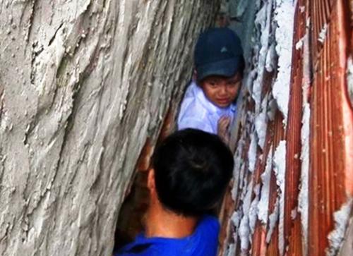 Cháu bé 8 tuổi được cảnh sát phá tường giải cứu. Ảnh: Thanh Liêm