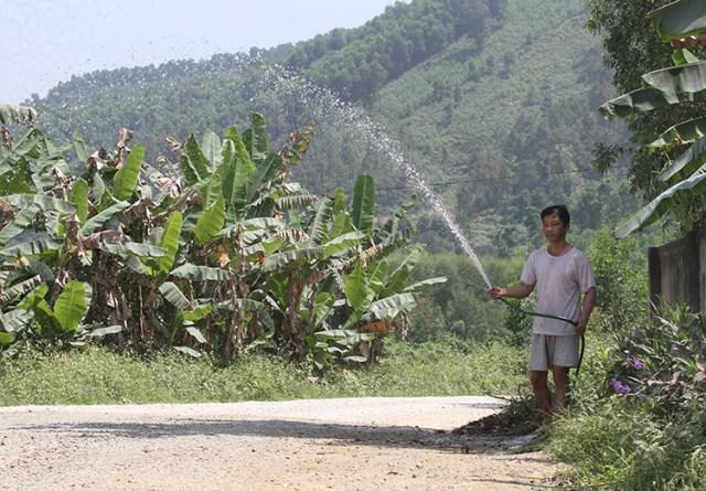Người dân phải phun nước cho đỡ bụi mỗi khi xe tải chạy qua khu vực nhà ở. Ảnh: Đức Hùng