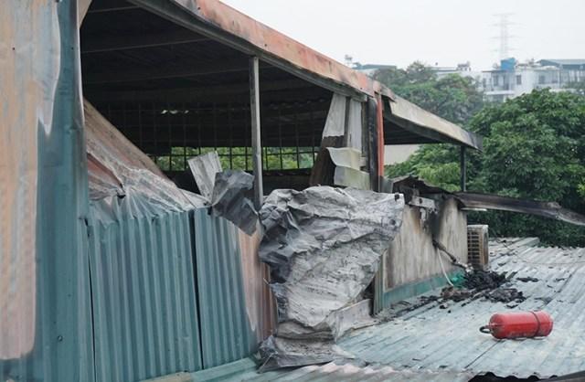 Căn nhà bốc cháy quây kín bằng tấm tôn. Ảnh: Nguyễn Định.