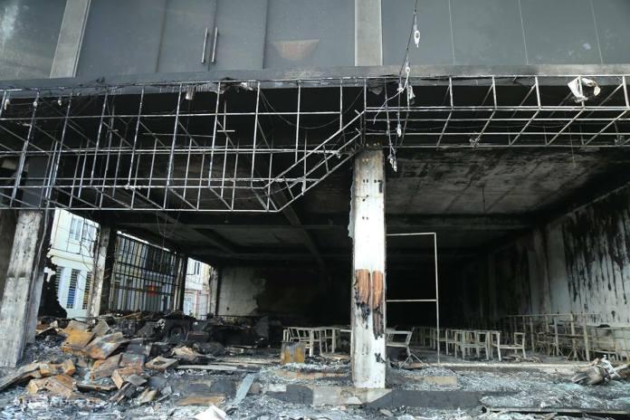 Ngọn lửa thiêu rụi bàn ghế, vật dụng bên trong phòng trà. Ảnh: Nguyễn Hải.