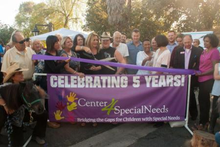 Gina Giambi Peters and her son Nathaniel (center) celebrate five years at an open house for Center 4 Special Needs.