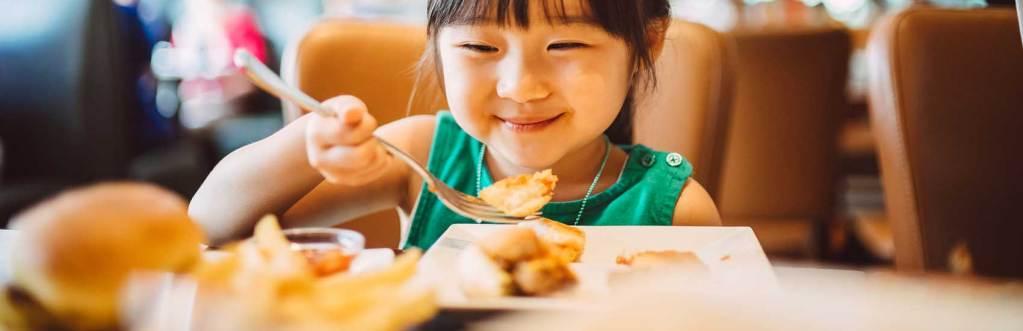 Child Enjoying Her Restaurant Meal
