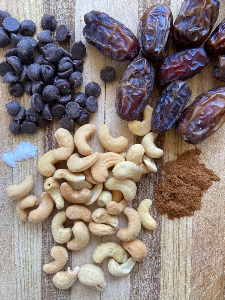cashews dates cinnamon salt and chocolate chips on wooden cutting board - how to make date balls