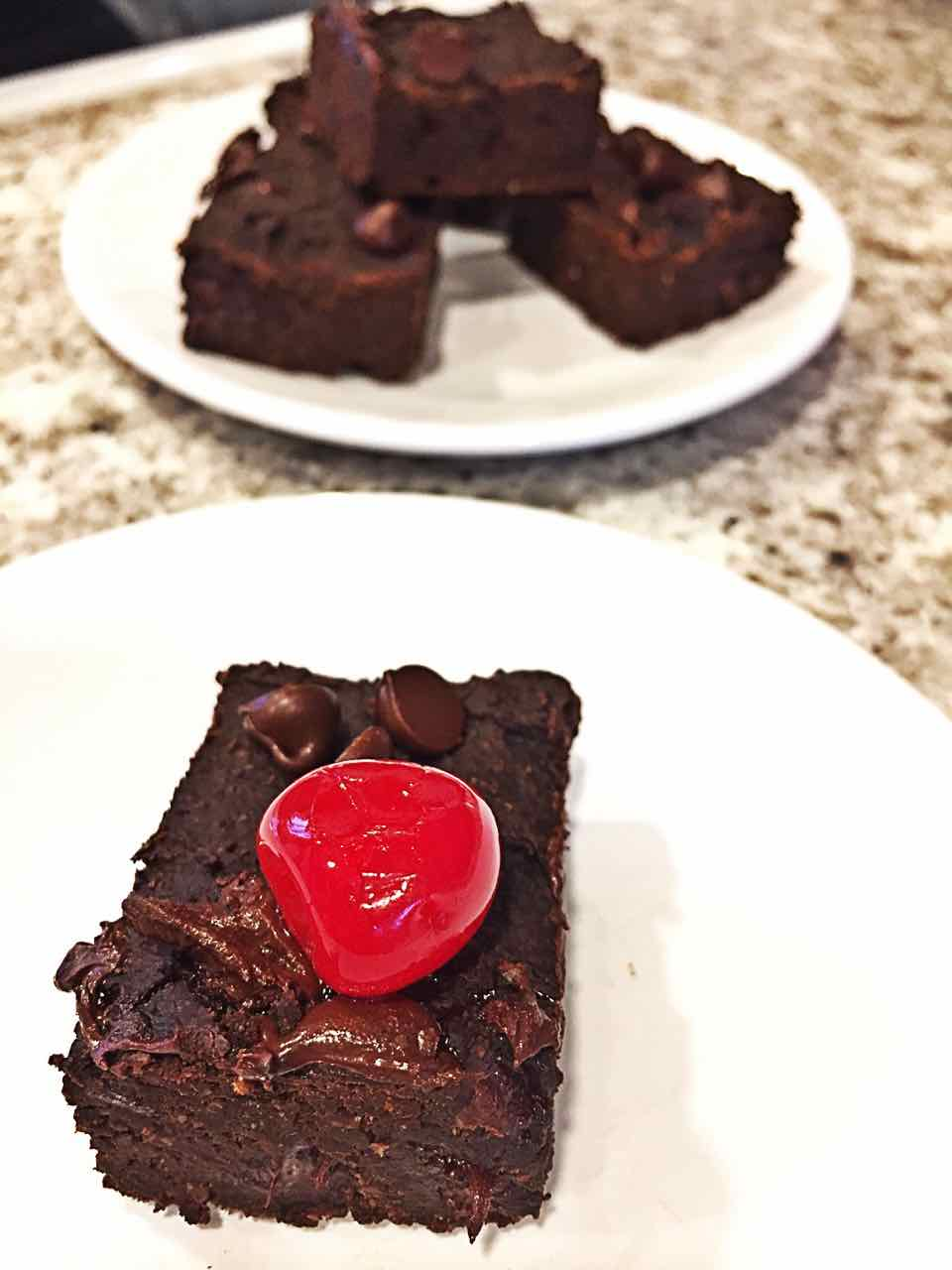 Image of gooey delicious vegan brownie with a cherry on top.