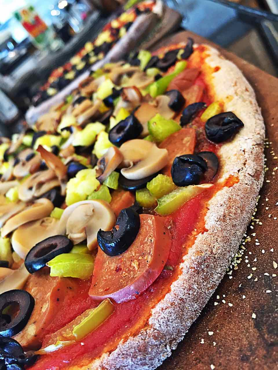 Image of vegan pizza, with focus on the crust. Pizza has vegan sausage, mushrooms, black olives, pineapple, and green peppers with homemade fast no rise whole wheat crispy and delicious pizza crust.