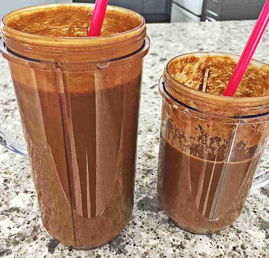 Image of two dark brown Chocolate Banana Green Smoothies, featuring spinach and cocoa powder.