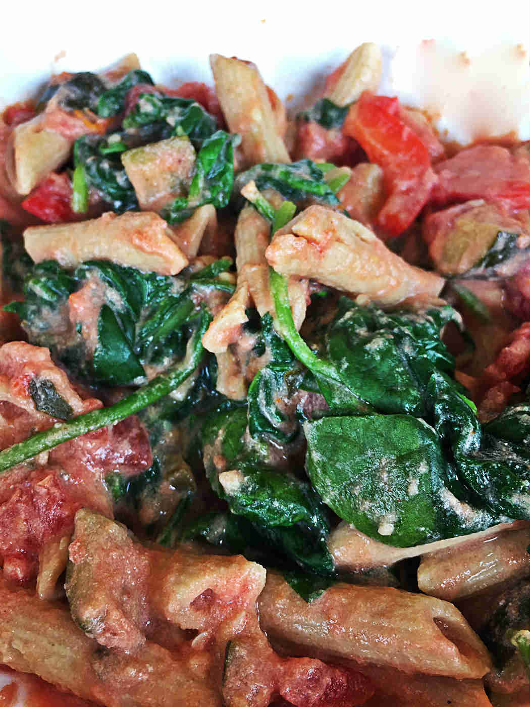 Image of spinach melted in with the creamy tofu pasta sauce and whole grain penne.