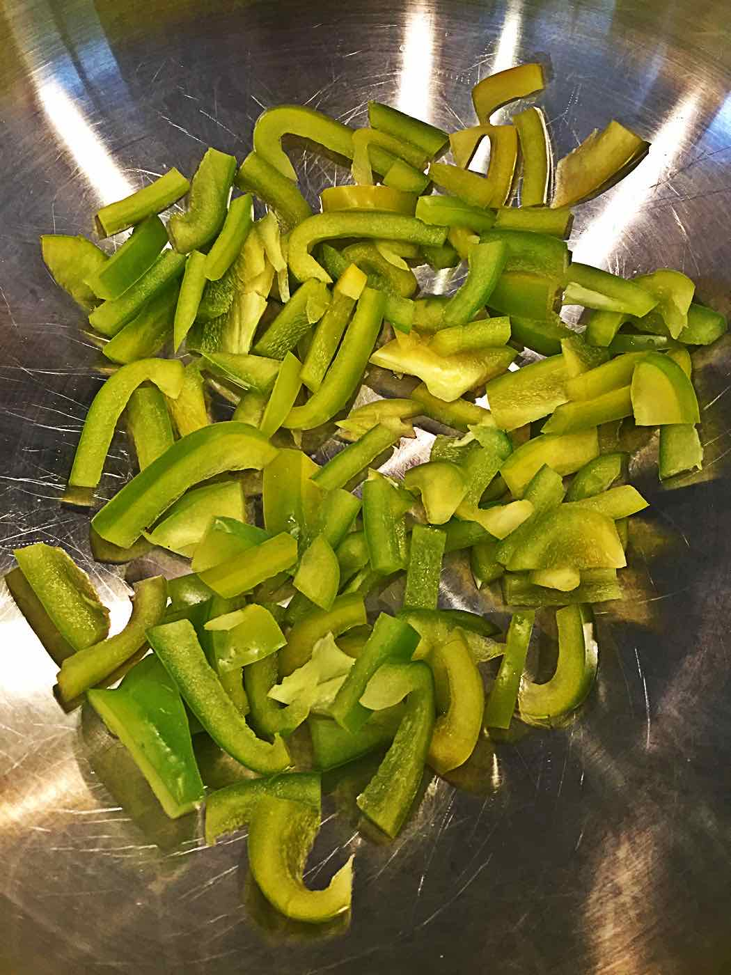 Sliced green peppers in a wok - VeganEnvy.com