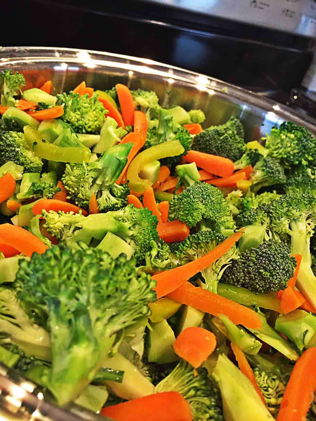 Sliced Broccoli carrots and green peppers for vegan no oil stir fry in wok
