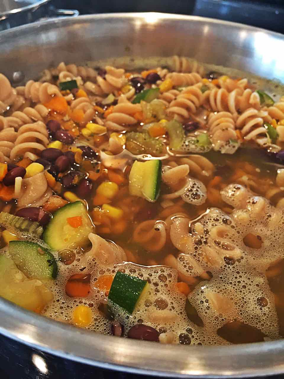 Image of vegan vegetable medley soup with vegetable broth in pot.