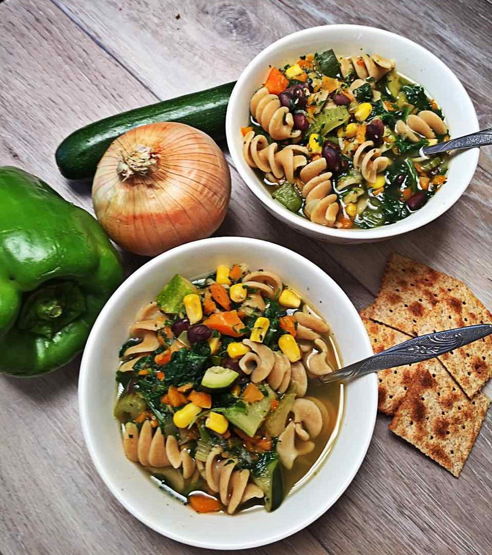 Image of Vegan Green Vegetable Medley green pepper, zucchini, spinach, corn, black bean, basil and oregano soup in bowls with crackers.
