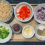 pre-cooked white beans, chopped red pepper, chopped onion, spices and salt, garlic and ginger, harissa paste, chopped spring onions