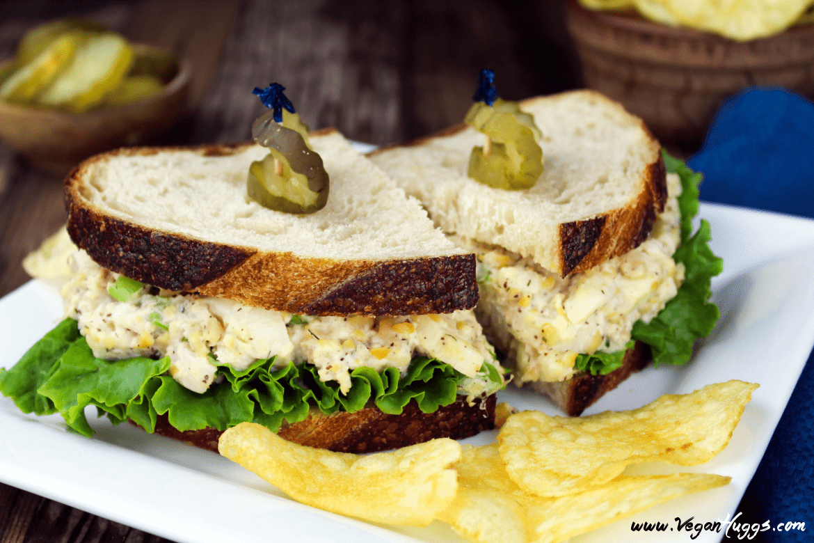 Side view of assembled sandwich on a plate with chips and pickles on the side.