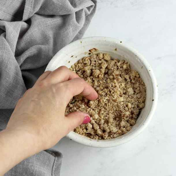 Making streusel crumble in a white bowl.