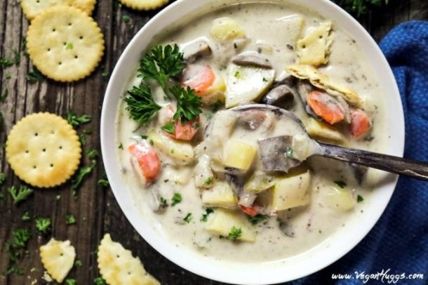 Close up photo of vegan clam chowder in a white bowl. Spoon in the bowl with mushrooms on top.