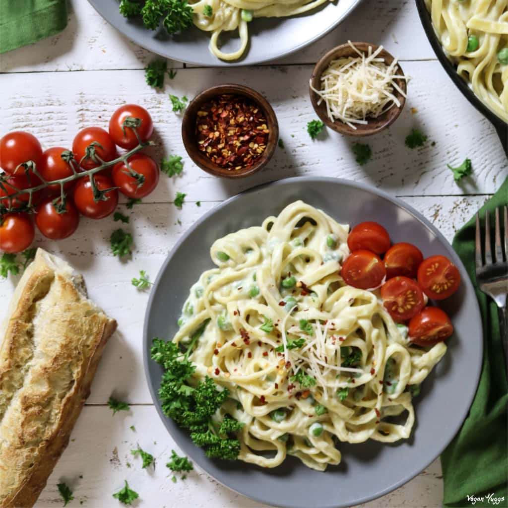 Overhead view of vegan fettuccine alfredo on a gray plate. Side of crusty bread and tomatoes.