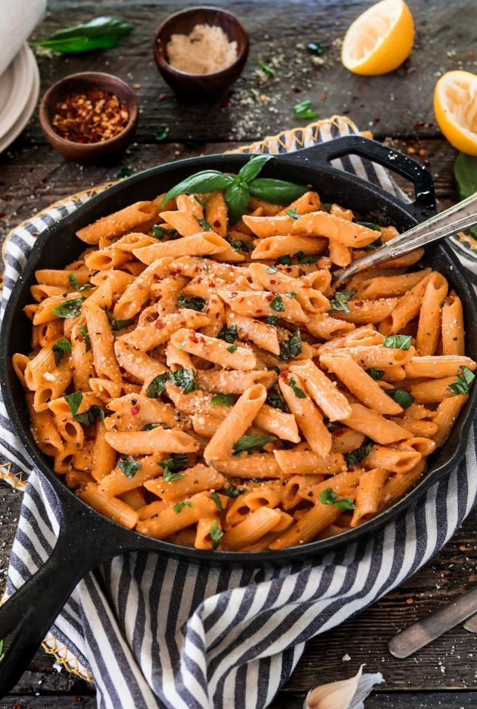 Vertical photo of roasted red pepper pasta in a cast iron skillet.