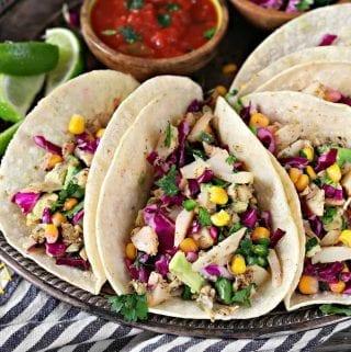 Horizontal photo of five vegan fish tacos on a tray.
