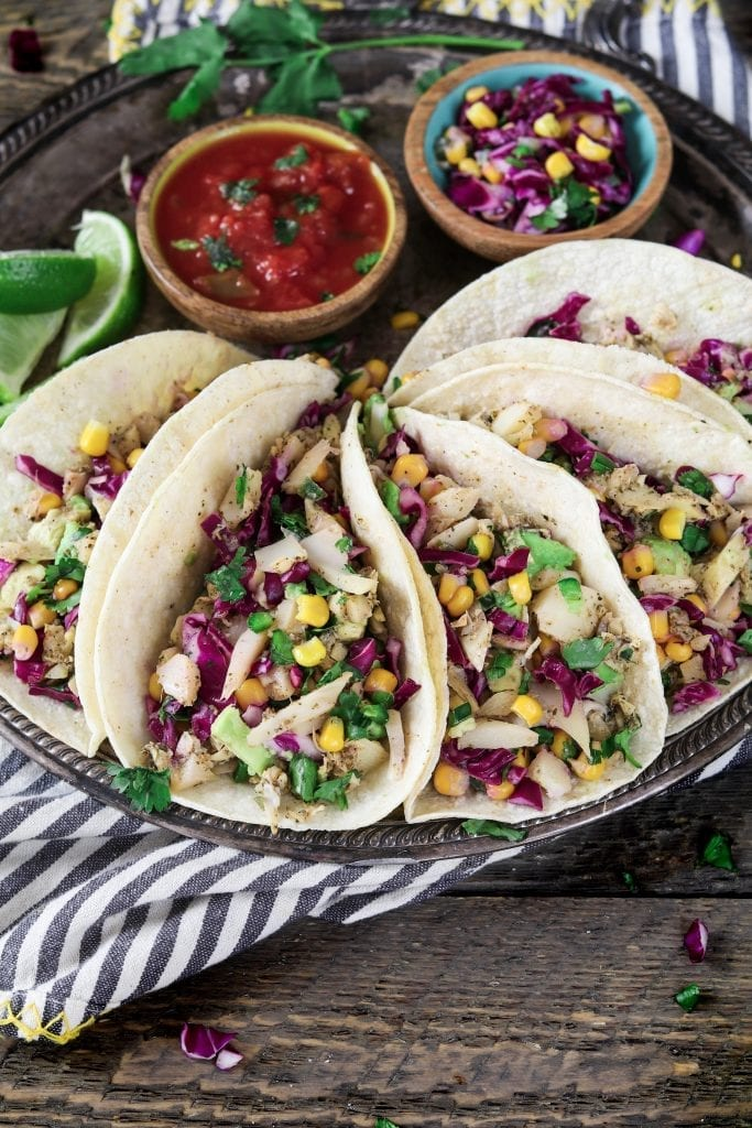 Vertical photo of five Vegan Fish Tacos on a tray.