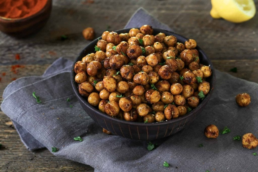 Horizontal photo of air fried chickpeas in a black bowl on top of grey napkin.