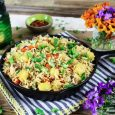 Rice in a skillet with flowers and green candle in the background.
