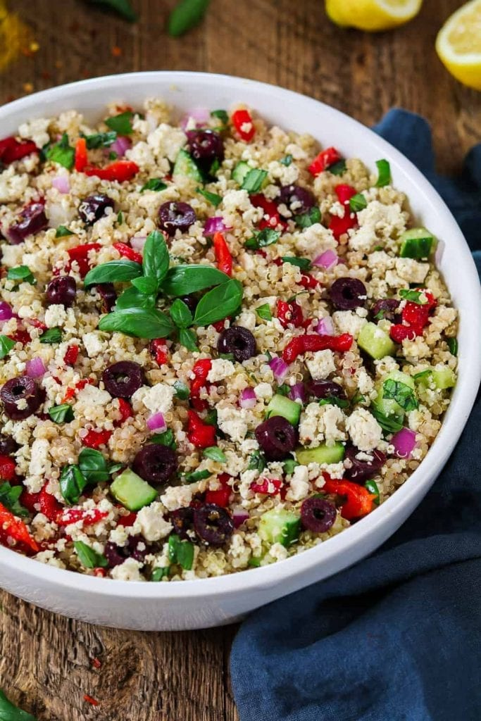Mediterranean Quinoa Salad in a large white bowl, topped with fresh basil sprigs.