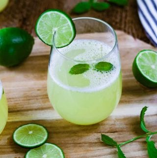 A glass of Fresh Limeade Recipe on a wooden cutting board. Mint and lime wedges on the board.