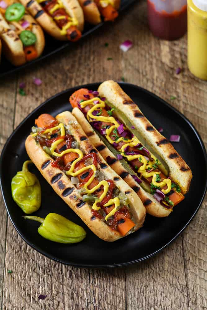 Overhead photo of two Vegan Carrot Hot Dogs on a black plate. Ketchup and mustard in the background.
