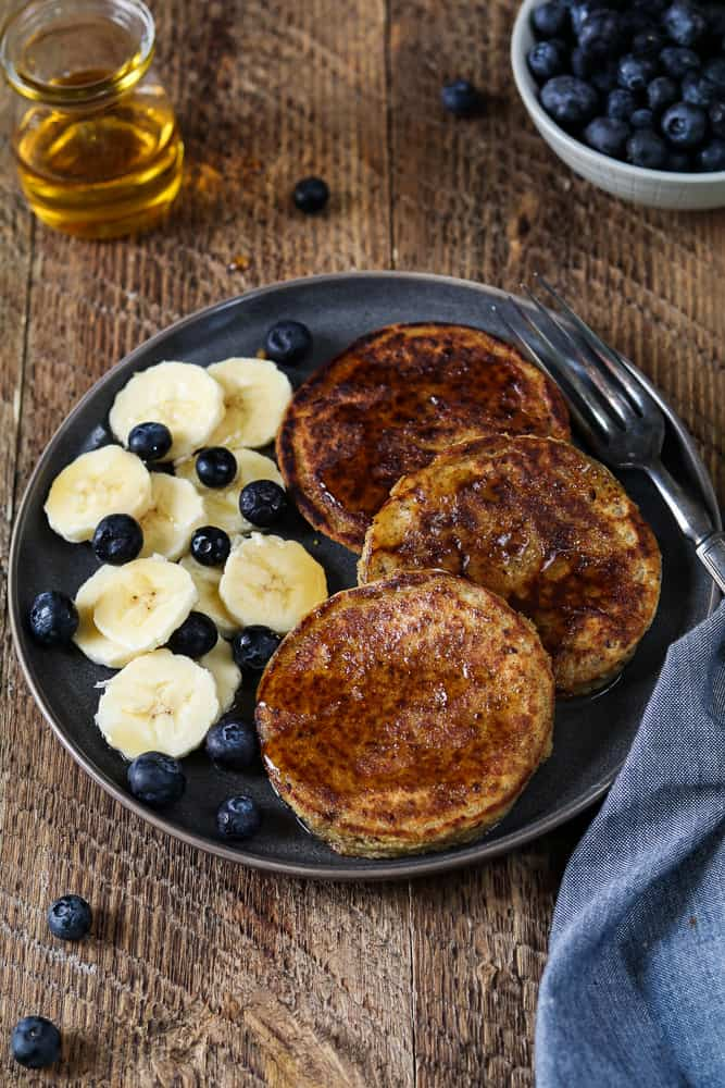 3 Vegan protein pancakes on a gray plate with banana coins and fresh blueberries on the side.