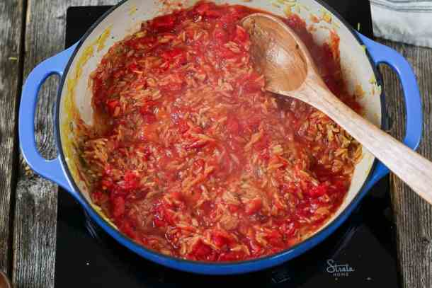 Fourth step - added the diced tomatoes into the blue pot. Wooden spoon to stir.