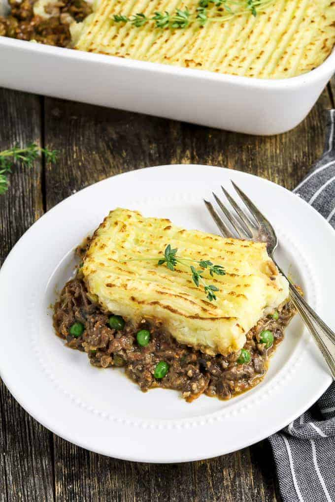 overhead view of a slice of vegan shepherd's pie on a white plate with a fork on the side.
