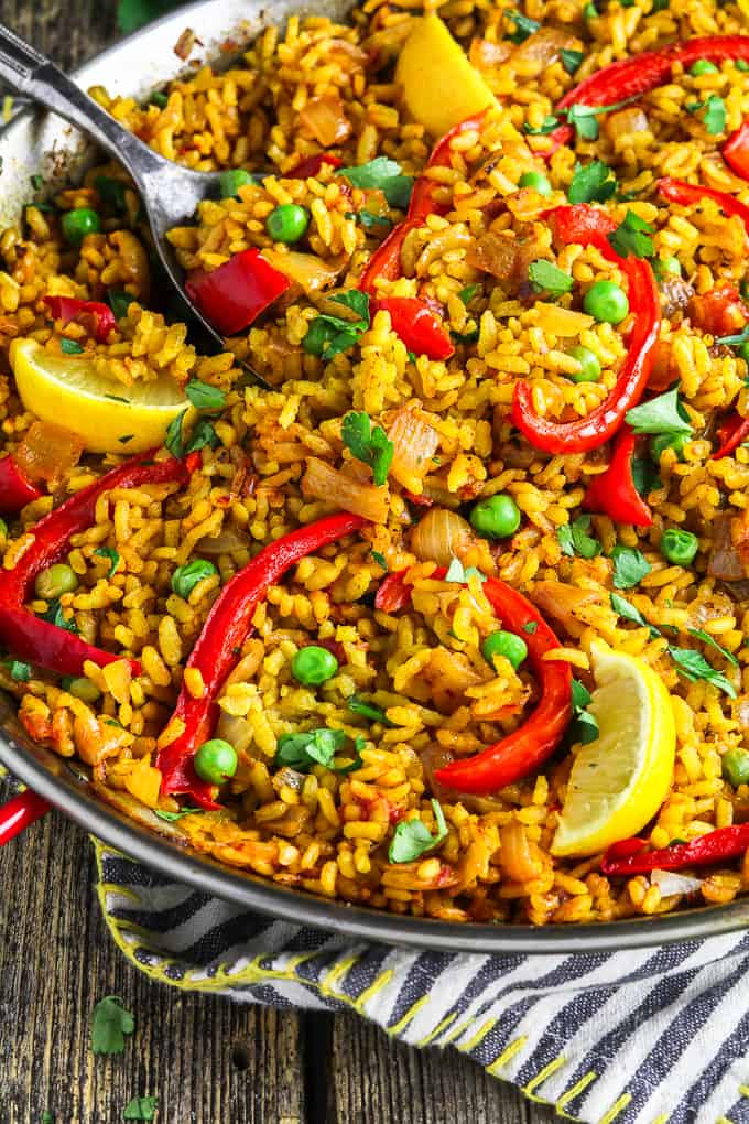 Close up view of vegan paella in a pan on top of a striped napkin.