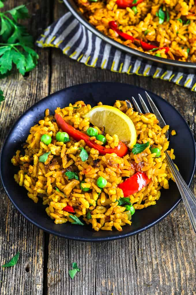 vegan paella on a black plate with a fork on the side.