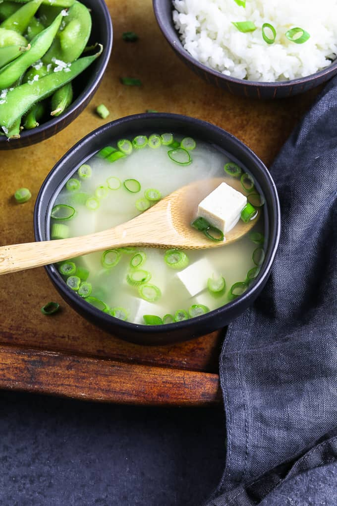 Tofu on a wooden spoon that's in a bowl of vegan miso soup. Edamame and rice on the side.