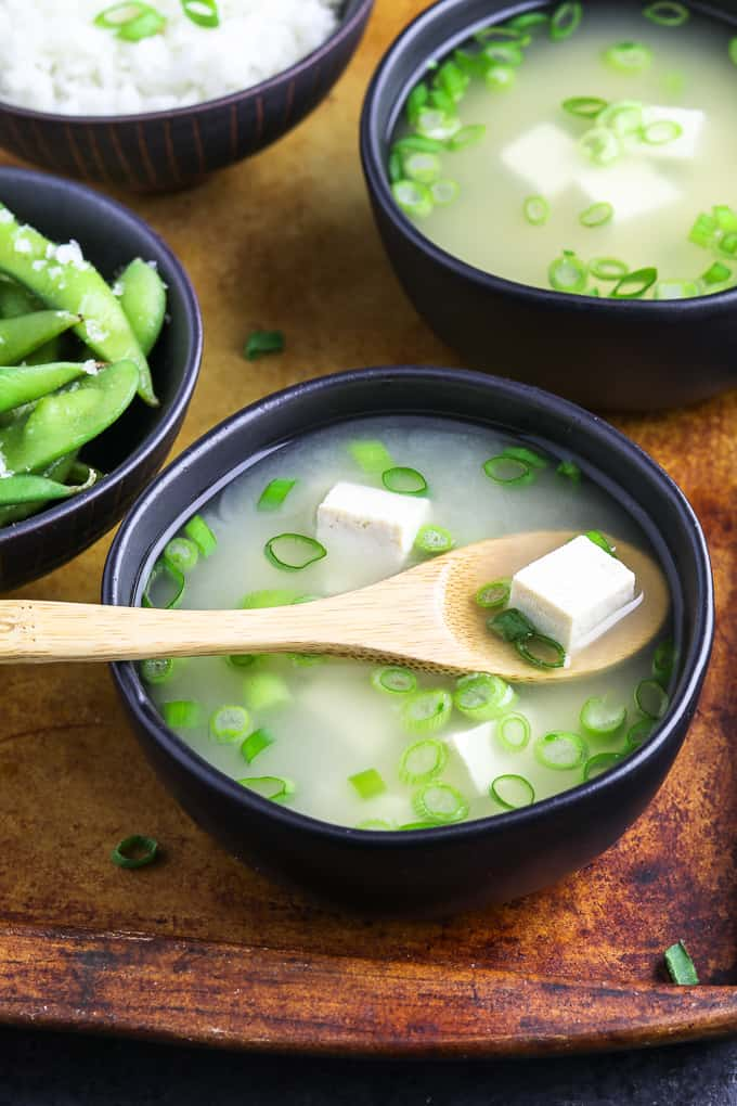 two bowls of soup on a serving tray with two bowls of rice and edamame on the side.