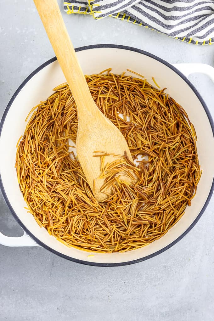 Browned fideo noodles in a large soup pot.