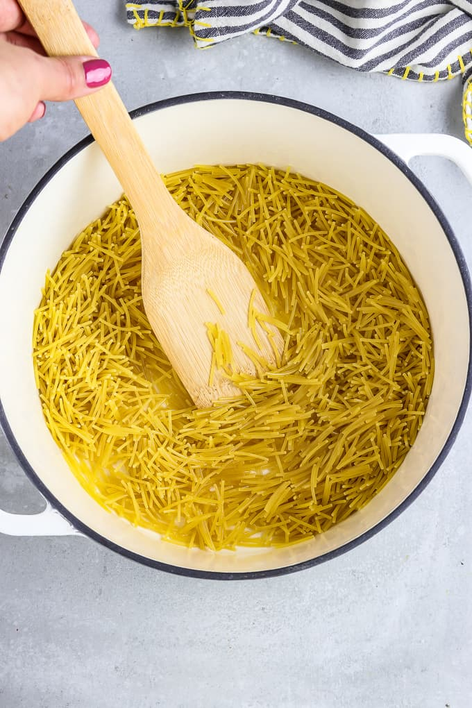 Stirring fideo noodles in a large pot with a wooden spatula.