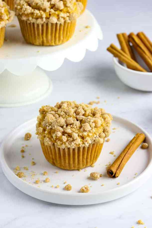 One baked muffin on a white plate with vegan pumpkin muffins on a cake stand in the background.